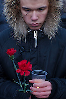 Moscow, Russia, 27/01/2011..A man holds a candle and flowers at a memorial ceremony in central Moscow for the 35 people killed in the Domodedovo airport bombing.