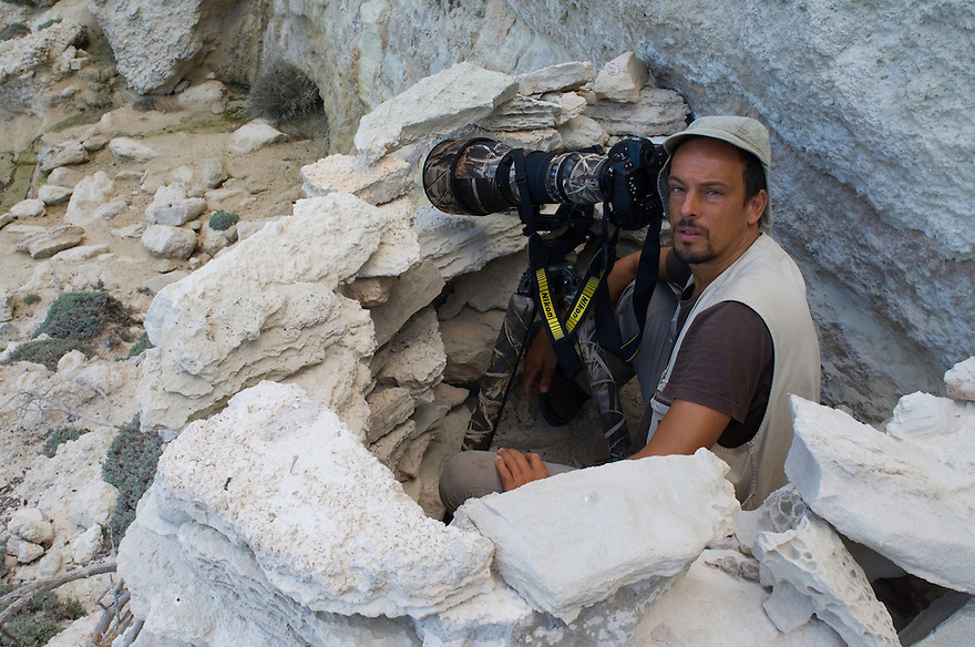 Photographer Stefano Unterthiner in his stone hide in Greece for WWE for his mission on Eleonora's falcon. Antikythera island, Greece.