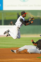 Kannapolis Intimidators shortstop Tim Anderson (2) flies through the air as he turns a double play against the Hickory Crawdads at CMC-Northeast Stadium on July 26, 2013 in Kannapolis, North Carolina.  The Intimidators defeated the Crawdads 2-1.  (Brian Westerholt/Four Seam Images)