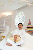 Interior designer Eggarat Wongcharit on the hanging banquette in the living/dining area he designed for the Villa Siam at Iniala