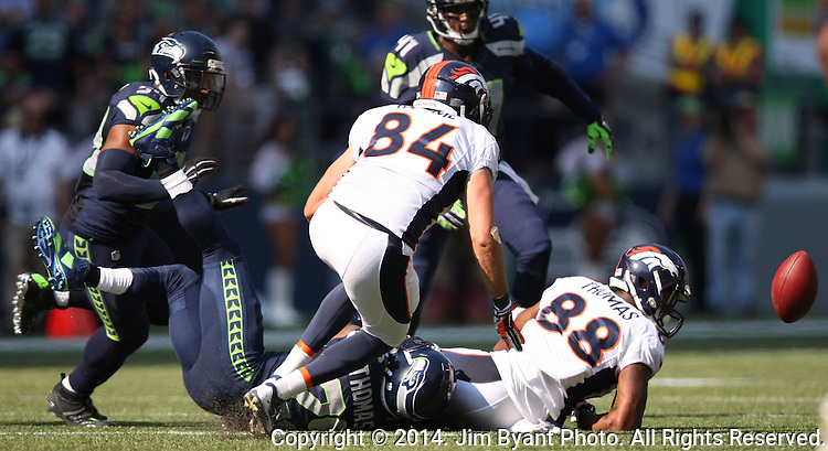 Denver Broncos wide receiver Julius Thomas (88) fumbles the ball after getting hit by Seattle Seahawks  free safety Earl Thomas at CenturyLink Field in Seattle, Washington on September 21, 2014. The Seahawks won 26-20 in overtime.  Seahawks linebacker Bobby Wagner recovered the fumble.  ©2014. Jim Bryant Photo. All rights Reserved.