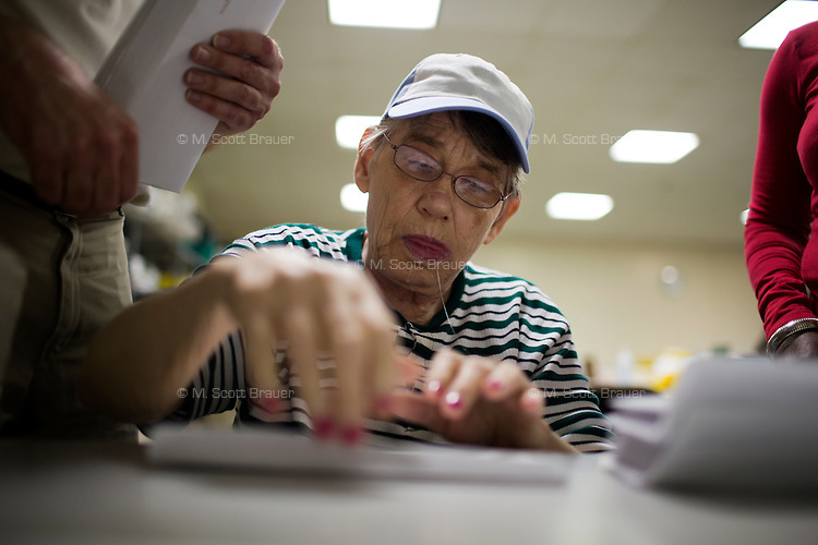 With the assistance of caretaker Georgette Thelismond (in red), Fernald resident Marilyn Davidson folds papers and stuffs envelopes for pay during work time at Site 7 at the Fernald Developmental Center in Waltham, Mass., USA.