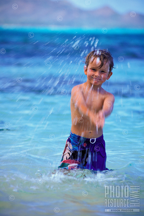 A young boy plays in the clear blue ocean on the windward side of Oahu.