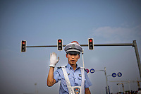 A Chinese police officer waves in Shenyang, China, Sunday, Aug. 10, 2008 during the Olympics...Photo by Roberto Candia