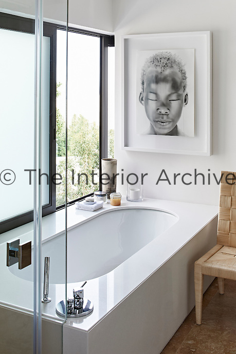 This contemporary house is an exercise in purity and harmony, where restraint and bleached colour allow simplicity and custom-made comfort to come to the fore as a luxury. A stylish bath beneath a window in one of bathrooms.