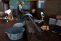KHUTSONG, SOUTH AFRICA - OCTOBER 16: A man makes  buckets for washing or bathing on October 16, 2012, in Khutsong, South Africa. Khutsong, a black township. is located about 56 miles west of Johannesburg, and surrounded by gold mines. Because of recent strikes many mineworkers has been fired which is making the poverty worse here. He sells them around the squatter camp to make some money. (Photo by Per-Anders Pettersson)