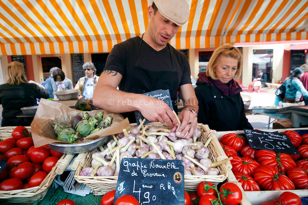 Chef Giorgio Grilenzoni of 'Chat Noir, Chat Blanc' restaurant chooses garlic bulbs at the Cours Saleya market, Nice, France, 10 April 2012