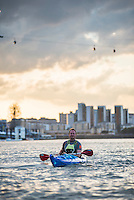 Kayaking at sunset under the Emirates Air Line Cable Car across the River Thames, Greenwich, London, England