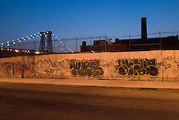 Williamsburg, Brooklyn, Cityscape at Dusk....Street, sidewalk, wall wiith graffiti, Williamsburg Bridge and landmarked Domino Sugar refinery (built in 1884)