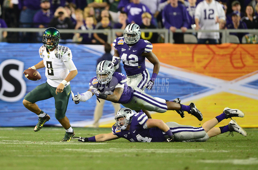 Jan. 3, 2013; Glendale, AZ, USA: Oregon Ducks quarterback Marcus Mariota (8) runs the ball as Kansas State Wildcats linebacker Justin Tuggle (2) and defensive end Ryan Mueller (44) dive in an attempt to tackle him during the 2013 Fiesta Bowl at University of Phoenix Stadium. Oregon defeated Kansas State 35-17. Mandatory Credit: Mark J. Rebilas-