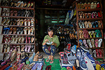 A woman eats while waiting for customers in her shoe stall in the Tahan Market in Kalay, a town in Myanmar. This market is located in Tahan, the largely ethnic Chin section of the town.