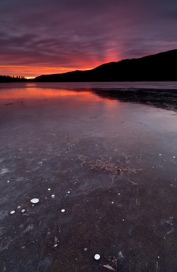 The sun rises as seen from a frozen pond, near Blanchard, Idaho