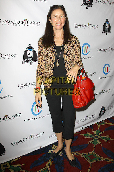 "MIMI ROGERS .Children's Institute Hosts ""Poker For A Cause"" Celebrity Poker Tournament held At Commerce Casino Hotel, City Of Commerce, California, USA..October 17th, 2009.full length black cropped trousers leopard print jacket red bag purse .CAP/ADM/KB.©Kevan Brooks/AdMedia/Capital Pictures."