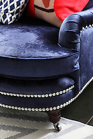 A plush velvet sofa in dark blue with silver studded decoration in the playroom
