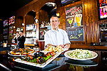 Progress Ridge B.J. Willys Woodfired Pizza & Pub General Manager Warren Marks is surrounded by dishes of calamari, bacon-wrapped stuffed jalapeño, pizza and Caesar salad which all can be served until the restaurant is closed....Photo by Jaime Valdez... ..