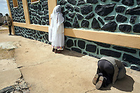 Eritrea. Maekel province. Asmara. St Michael church. A black woman, wearing white clotes and a white veil on her head to cover her hair ( cotton loincloth) and two men are praying on St Michael's day during an orthodox religious service. One man is on his knees on the groung. The woman is standing in front of a wall and is kissing the black wall's stones.  © 2006 Didier Ruef