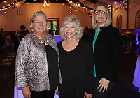NWA Democrat-Gazette/CARIN SCHOPPMEYER Cindy Hudlow (from left), Nancy Hairston and Teresa Taylor welcome guests to the Haute Trash Fashion Show to benefit the Elizabeth Richardson Center on May at Sassafras Springs Vineyard and Winery in Springdale.