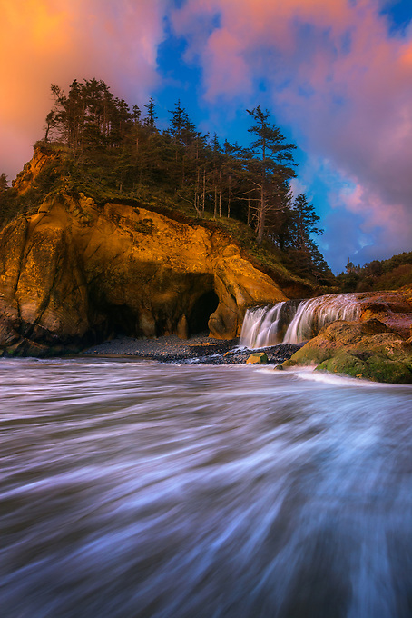 The setting sun reflected onto a unique location on Oregon's northern coast, where a waterfall flows off a small cliff into the incoming tides of the Pacific Ocean.