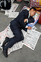 A job seeker takes a rest outside the Guangzhou Railways station at the beginning of the Chinese New Year. Millions of workers pass through this station mostly on the way to factory  production and construction projects in Guangdong Province, China..17 Mar 2007.