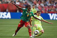 June 12, 2015: Yvonne LEUKO of Cameroon and Nahomi KAWASUMI of Japan compete for the ball during a Group C match at the FIFA Women's World Cup Canada 2015 between Cameroon and Japan at BC Place Stadium on 12 June 2015 in Vancouver, Canada. Japan won 2-1. Sydney Low/AsteriskImages