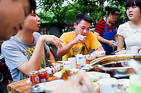 A group of friends who live in the neighborhood eat at He Wang Shi Chuan Chuan Xiang Huo Guo, a skewer-style hotpot restaurant popular with locals on Tiyu Road in Chongqing, China. The girl in white, who asked not to be named, said that it's one of their favorite places the hotpot flavor is so good.  &quot;We like the atmosphere. It's a typical Chongqing place: friends sit together and it's hot out and you all sweat together.&quot; She works in real estate and thinks that places like this won't survive as neighborhoods develop.<br /> <br /> Individual servings of meat, vegetables, and tofu, are placed on skewers which diners choose to add to their table's hotpot. The restaurant, which has many favorable online reviews, often has a long wait for tables.