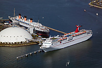 aerial photograph of the Queen Mary and the Carnival cruise ship, Paradise, at the Long Beach cruise terminal, Long Beach, Los Angeles County, California
