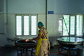 A worker takes fire to cook oil with herbs at the Pharmacy of the National Research Institute of Panchakarma in Cheruthuruthy in Thissur district of Kerala, India.