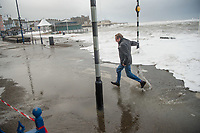 Pictured: A man is caught up in water caused by waves that crash against the seaside town of Aberystwyth, Wales, UK. Saturday 21 October 2017<br /> Re: Coastal parts of the UK is facing winds of up to 70mph as Storm Brian causes roads to close and public transport to be cancelled.<br /> Roads in Aberystwyth's seafront and at nearby Aberaeron, Wales are shut on Saturday morning as a yellow &quot;be aware&quot; Met Office warning is in place.<br /> Seven flood warnings have been issued for the west Wales coast.
