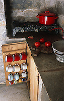 Red and white enamel mugs are stored in rows inside a kitchen cupboard door