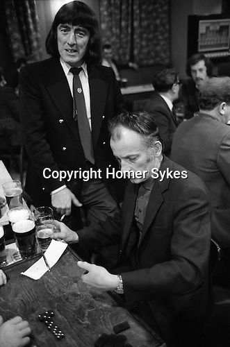Playing dominos Saturday night at Byker & St.Peters Working Men's Social Club Newcastle upon Tyne, Tyne and Wear northern England 1973. Typically men dressed up to go out for the evening. 1970's fashion a Beatles haircut ( in the style of John, Paul, George and Ringo ) a blue double breasted blazer with brass buttons a collar and tie.