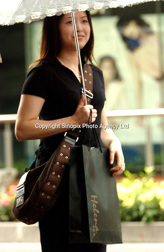 "A shopper outside a Fendi shop at the ""La Perle"" upmarket shopping center in Guangzhou, China. The Guangzhou La Perle shopping center collected most global top rank brand names, including Prada, Louis Vuitton, Christian Dior and Hermes..23-APR-04"