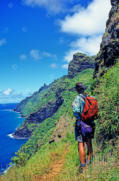 Backpacker on the Kalalau Trail enjoys grand view of Kauai's Na Pali Coast.