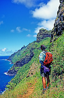 Backpacker on the Kalalau Trail enjoys grand view of Kauai's Na Pali Coast.