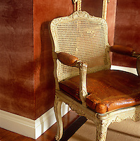 The leather cushion on a cane-backed antique armchair is the same colour as the burnt-cinnamon of the velvet wall behind