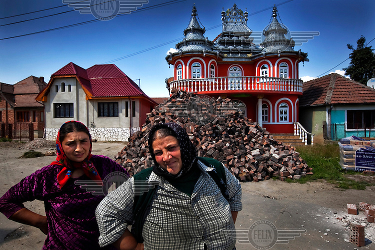 Two Roma women proudly show-off their newly constructed  palace.