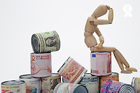 Depressed wooden mannequin on messy tin cans. Cans are surrounded by world wide international banknotes symbolizing the international finance crisis and  the currencies exchange rate competition, on white background, studio shot (Licence this image exclusively with Getty: http://www.gettyimages.com/detail/102170469 )