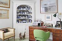 A cosy study room with a collection of blue and white china displayed in a built-in alcove corner cupboard. A painting by Terence Flanagan hangs above the traditional wooden knee-hole desk. A retro green chair brings a spot of colour to the room.