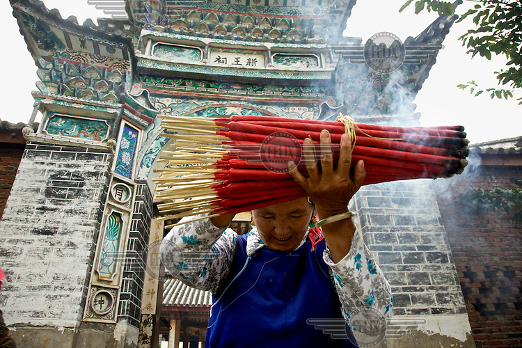 A woman raises a big bunch of burning incense as she offers prayers at a village temple. /Felix Features