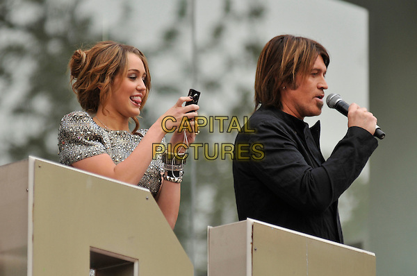 "MILEY CYRUS & BILLY RAY CYRUS .Attending the UK Film Premiere of ""Hannah Montana: The Movie"" at the Odeon cinema Leicester Square, London, England, UK, April 23rd 2009..half length speaking microphone father daughter balcony family dad lack silver grey gray camera taking picture photo .CAP/PL.©Phil Loftus/Capital Pictures"