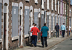 Two supporters walking past boarded up and derelict houses in a street adjacent to Anfield, home of Liverpool football club, pictured before the club took on Fulham in a Premier League match during the 2009-10 season. The club was one of the most successful and best supported teams in England and which won many domestic and European trophies. The most-famous part of the stadium was the Kop, where the Liverpool fans sat during games. Photo by Colin McPherson