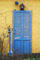 A blue wooden old door against a yellow wall. at the restaurant La Estacada on the waterside Montevideo, Uruguay, South America