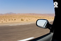Side-view mirror of car speeding on desert highway (Licence this image exclusively with Getty: http://www.gettyimages.com/detail/sb10065145be-001 )