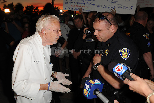 FORT LAUDERDALE, FL - NOVEMBER 12: Fort Lauderdale Police Officer, Sgt. Al Lerner speaks with Arnold Abbott, (L) a 90-year-old chef , as he warns him that he will be cited for feeding homeless in violation of a recently passed city law on November 12, 2014 in Fort Lauderdale, Florida. The city said they passed the ordinance for sanitary and security reason, but Mr. Abbott continued to feed the homeless in a city park where he has twice been cited for violating the new ordinance.  Credit: mpi04/MediaPunch