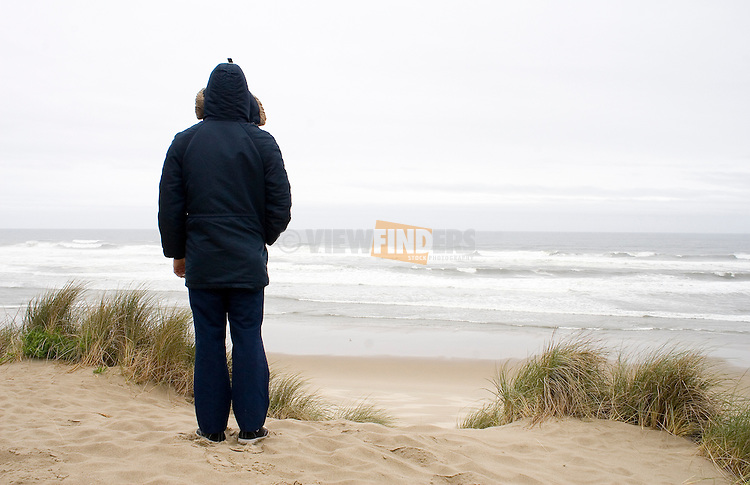 man watching the ocean from a sand dune