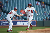 Brady Lindsly (40) of the Oklahoma Sooners shakes hands with third base coach Clay Van Hook (19) after hitting a home run against the Arkansas Razorbacks in game two of the 2020 Shriners Hospitals for Children College Classic at Minute Maid Park on February 28, 2020 in Houston, Texas. The Sooners defeated the Razorbacks 6-3. (Brian Westerholt/Four Seam Images)