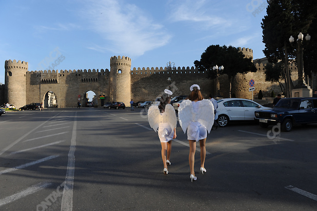 "Women dressed as ""angels"" walked towards the gates of the old city of Baku, Azerbaijan, May 15, 2001"