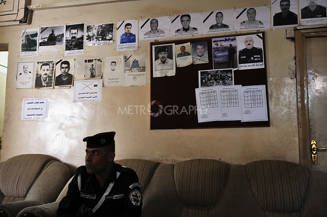 KIRKUK, IRAQ: A policeman sits in front of a wall photographs of policeman who've been killed in Kirkuk. Since 2003, 153 provincial policeman have been killed and 257 wounded...Kirkuk, the oil-rich city in northern Iraq, is home to Kurds, Arabs, Turkomen, Christians, Kakayi, and numerous other ethnicities. Since 2003, thousands of its residents have been killed or injured in terrorist attacks...As the US military leaves Iraq, the future of this violent and ethnically diverse city remains unsure...Photo by Pazhar Mohammad/Metrography