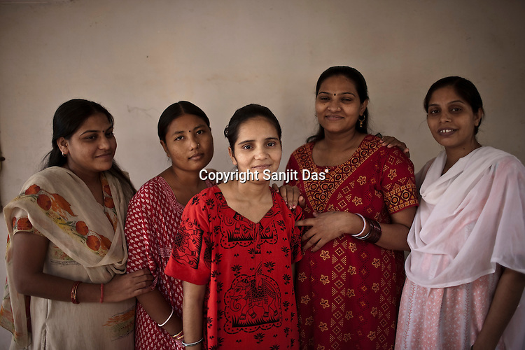Pregnant as a surrogate mother for first time, 20 year old Vaishali Sanket poses for photograph with other surrogate mothers in the background in Rabina's house in Anand, Gujarat, India. Rabina now mentors surrogate mothers and houses women throughout theior pregnancy.