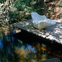 A contemporary chaise-longue stands on a shady deck overlooking a pond filled with Koi carp
