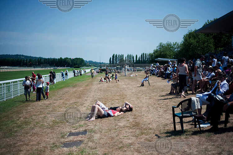 People relax on the grass between horse races at the Deauville Hippodrome.